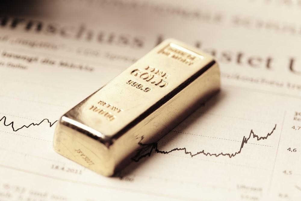 Goldbarren liegt auf Graph mit Aufwärtstrend